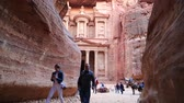 siq : JORDAN, PETRA, DECEMBER 5, 2016: People near Al Khazneh or the Treasury at the ancient Petra - historical and archaeological city in Hashemite Kingdom of Jordan. View from Siq - long narrow passage, gorge Stock Footage