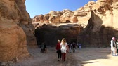 siq : JORDAN, PETRA, DECEMBER 5, 2016: People in the Siq - a narrow passage, gorge that leads to the Red Rose City of Petra, originally known to Nabataeans as Raqmu - historical and archaeological city in Jordan