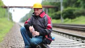 Workman sits on branch. Railway worker sits on railway line. Repairman in yellow hard hat with tools