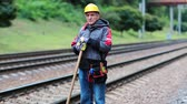 plodder : Repairman with shovel in hands on rail on and look at the camera. Railway worker with shovel in hands on the railway track. Workman with shovel on branch railway Stock Footage