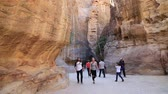JORDAN, PETRA, DECEMBER 5, 2016: People in the Siq - a narrow passage, gorge that leads to the Red Rose City of Petra, originally known to Nabataeans as Raqmu - historical and archaeological city in Jordan