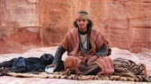 andarilho : JORDAN, PETRA, DECEMBER 5, 2016: Jordanian look at the camera, ancient Petra, originally known to Nabateans as Raqmu - historical and archaeological city in Hashemite Kingdom of Jordan Stock Footage