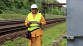 toiler : Repairman in yellow uniform on railway line. Electrician in white hard hat with tablet. Railwayman makes notes in his tablet computer