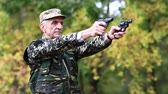 harcias : Senior man shoots a two pistols in forest. Soldier in the military uniform shoots from the two pneumatic handguns. Soldier in military uniform shoots a revolver. Retired officer at shooting range
