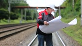 whatman : Railway worker with design drawings in hands stands on rail branch. Railwayman in white hard hat with work scheme in hands
