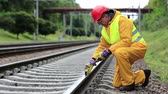 plodder : Railway worker in uniform. Railway man in red hard hat sits on railway tracks and looks at the train. Workman with level measuring instrument