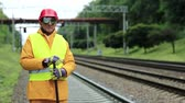 fixer : Railway worker in uniform. Railway man in red hard hat stands on railway tracks and looks at the camera. Workman with metal crowbar on railway track Stock Footage
