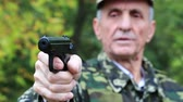 harcias : Soldier in military uniform shoots a revolver. Retired officer at shooting range. Senior man in the military uniform shoots a pistol in the forest. Man with black gun