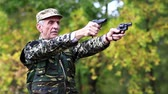 harcias : Soldier in the military uniform shoots from the two pneumatic handguns. Senior man shoots a two pistols in forest. Soldier in uniform shoots a revolver. Retired officer at shooting range. Video with sound