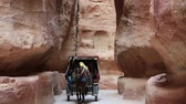 siq : JORDAN, PETRA, DECEMBER 5, 2016: People in a horse-drawn carriage in Siq - a narrow passage that leads to Petra, originally known to Nabataeans as Raqmu - historical and archaeological city in Jordan Stock Footage
