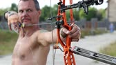 bowman : UKRAINE, KIEV REGION, KOPACHIV VILLAGE, AUGUST 14,2016: Archer shoots a bow at a target. Man training at archery with bow and arrow. Man hold bow in his left hand