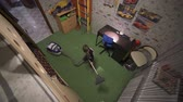 respeito : The boy is vacuuming in the room. Helps parents on home affairs. Top view.