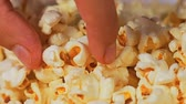 kernels : Close-up of popcorn background and a hand picks one piece of popcorn Stock Footage