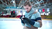 кататься на коньках : Young man with phone at skating rink