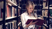 library : Young girl reading a book in library Stock Footage
