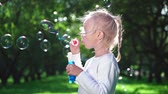 Little girl with soap bubbles in summer