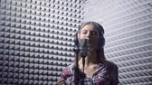 передача : Singing young girl in a recording studio