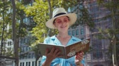 jornalista : Smiling woman with a memorial book in the park, NYC Vídeos
