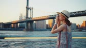 Нью Йорк : Young girl taking photo at Manhattan bridge in the evening