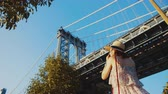 videocamara : Young tourist with a camera at the Manhattan bridge in New York Archivo de Video