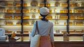 caps : Young girl at the shelves with perfume in a french store