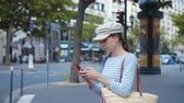 caps : Young tourist with a smartphone on a street in Paris Stock Footage