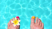 Seamless loop - Woman bare feet with frangipani flower, turquoise water in the background, HD video