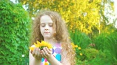bloom : Curly haired little girl enjoy with sunflowers in summer park.