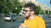 котлета : Bearded man greedily eating fresh tasty hamburger outdoors lunch break Стоковые видеозаписи