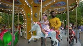 kolotoč : Mom, dad and little daughter are going on a merry-go-round