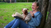 postura : Attractive woman reading a book in a Park by tree.A cute dog runs to her,slowmo
