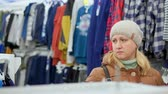 детский : A middle-aged woman in a winter coat and a hat goes to a childrens clothing store. Looks at the shelves Стоковые видеозаписи