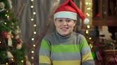 развлекать : A boy teenager in a hat Santa Claus is dancing near the Christmas tree. Christmas holiday, happy new year