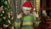 ожидая : The boy in the sweater and the hat of Santa Claus is upset and offended. He has no gift. Against the background of Christmas lights