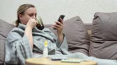 A woman has a cold at home. Lying on the couch with the phone