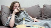 온도계 : Teen girl drinking medicine tea warm. Lying on the couch, covered with a blanket