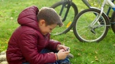 enfants jeux : Teenage boy sitting on the grass, playing smartphone. Vidéos Libres De Droits