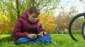 młodzież : Teenage boy sitting on the grass, playing smartphone. Wideo
