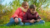 parques : Teen boy sitting on the grass and playing smartphone. Sitting next to mom Stock Footage