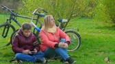 Teen boy sitting on the grass and playing smartphone. Sitting next to mom Dostupné videozáznamy