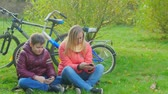 parques : Teen boy sitting on the grass and playing smartphone. Mom is sitting next