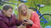 parques : Teenage boy sitting on the grass with his mother. Dependence on smartphones. Stock Footage