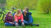 parques : Teen boy sitting with mom and dad on the grass