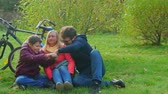 parques : Teen boy sitting with mom and dad on the grass. Smartphone addiction. Stock Footage