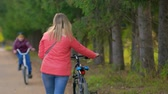 ciclismo : Woman walking with a Bicycle in the Park. Shes walking away from the camera Stock Footage