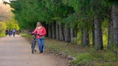 parques : Woman walking with a Bicycle in the Park.She goes to the cameras in the distance
