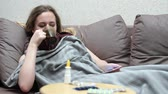 온도계 : Teen girl drinking medicine tea warm. Lying on the couch with a smartphone