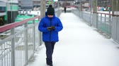 stadt straße : Boy teenager in blue down jacket on the street reads messages smartphone. Stock Footage