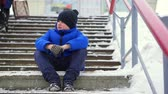 stadt straße : Boy teenager in blue down jacket lost in the city. He sits on a cold staircase, looks around.