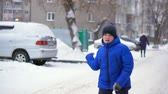 楽しんで : Boy teenager in blue down jacket throws a snowball. Winter, falling snow